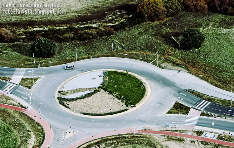 Fotografía tomada desde ultraligero volando por encima de una rotonda y carretera que cruza tierras de labranza a los lados en Villanueva del Pardillo, Madrid