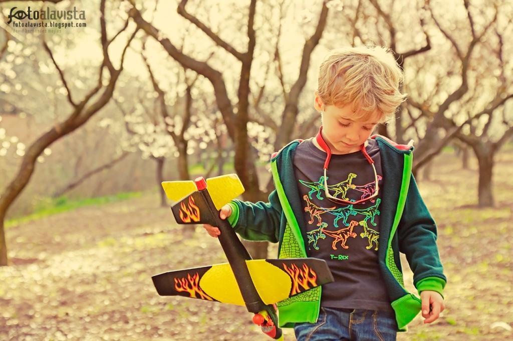 Niño con avión flamígero rodeado de almendros: #RetoNiños. Fotografía creativa - Fotografía infantil